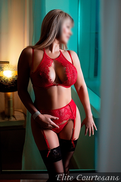 Blonde courtesan Holly looking gorgeous in red underwear, staring out of the window of her Oxford home.