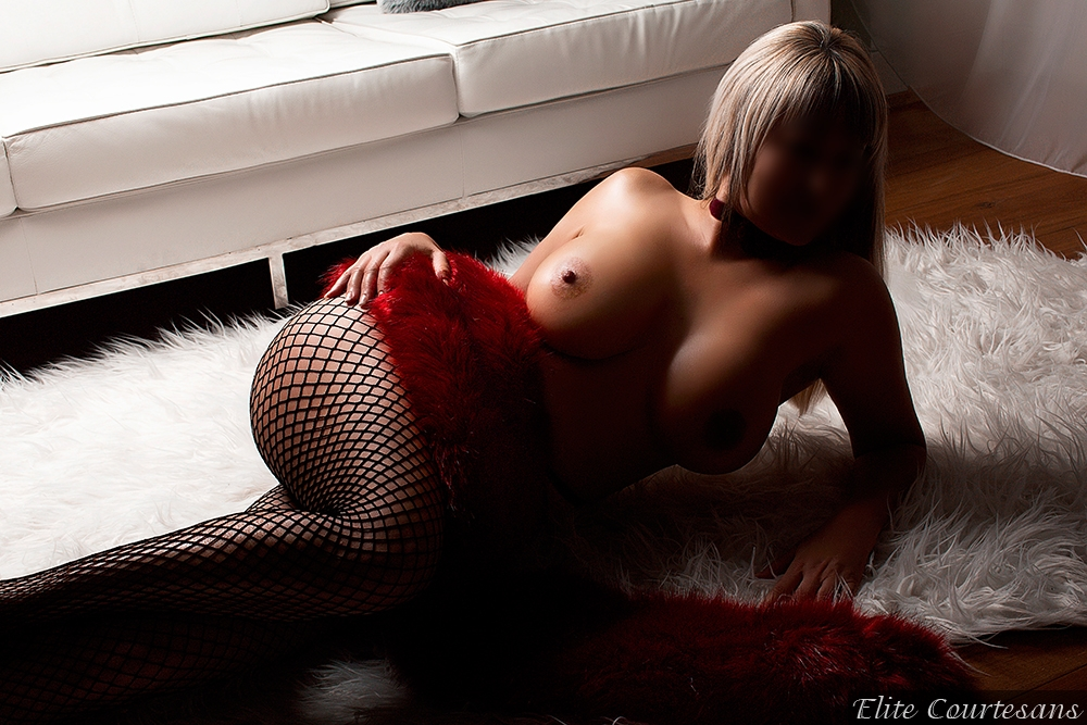 High class escort Holly lying seductively in fishnets on the floor of her Reading apartment.
