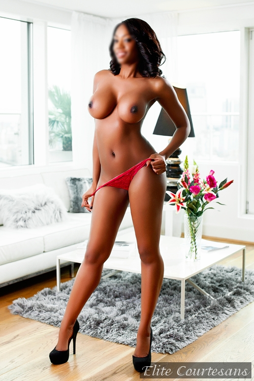 Black escort in London posing topless at a photoshoot