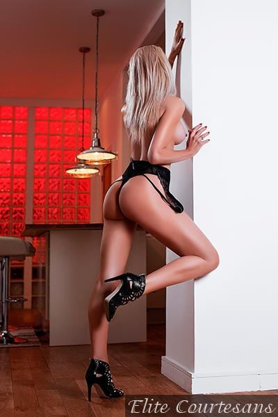 Melissa posing topless in very high heels.