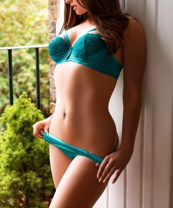 Beautiful brunette leaning against the dooryway in satin green knickers and bra, slowly pulling her knickers down.