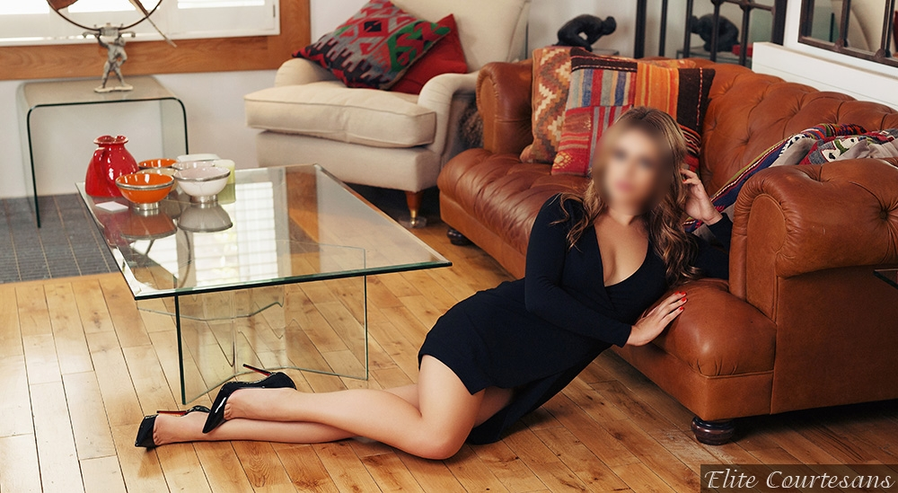 Looking incredible in a tight, fitted black dress, sat on the floor and leaning onto her Chesterfield sofa.
