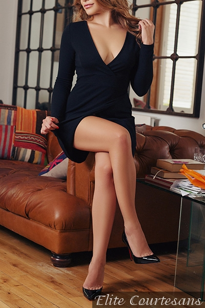 Birmingham NEC outcall escort sat on the edge of her Chesterfield settee in a little black dress and classic black high heels, twiddling her hair in her fingers.