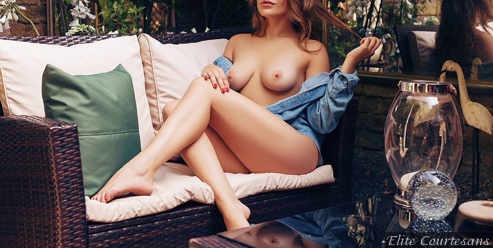 Georgia topless in her denim shirt lying on the rattan sofa in her Birmingham apartment.