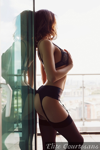 Stood in the window gazing out over the horizon in black lingerie and stockings.
