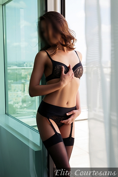Looking pretty in expensive, fashioned black lingerie and high heels.