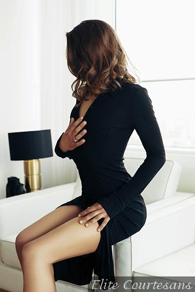 Bath escort Jade modelling her little black dress, brunette hair tumbling over her shoulders.