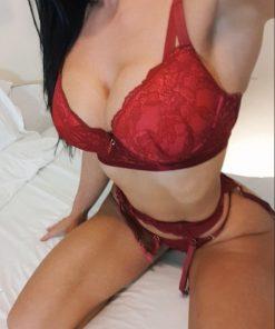 Birmingham escort Lauren kneeling in the bed in red lingerie that compliments her skin tone perfectly.